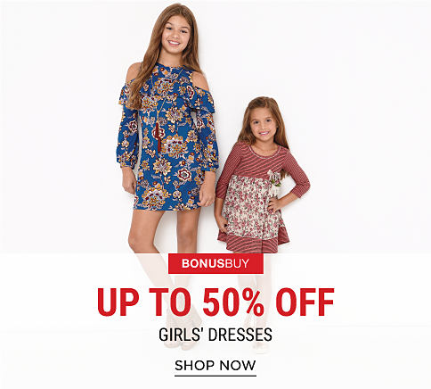 A girl wearing a multi-colored floral print cold-shoulder dress standing next to a girl wearing a maroon & white striped dress with a floral print on the skirt. Bonus Buy. Up to 50% off girls' dresses. Shop now.
