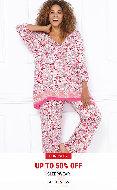 A woman wearing pink & white patterned pajamas. Bonus Buy. Up to 50% off sleepwear. Shop now.