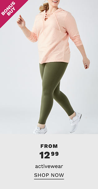 A woman wearing a peach hoodie, olive green yoga pants & white sneakers. Bonus Buy. From $12.99 activewear. Shop now.