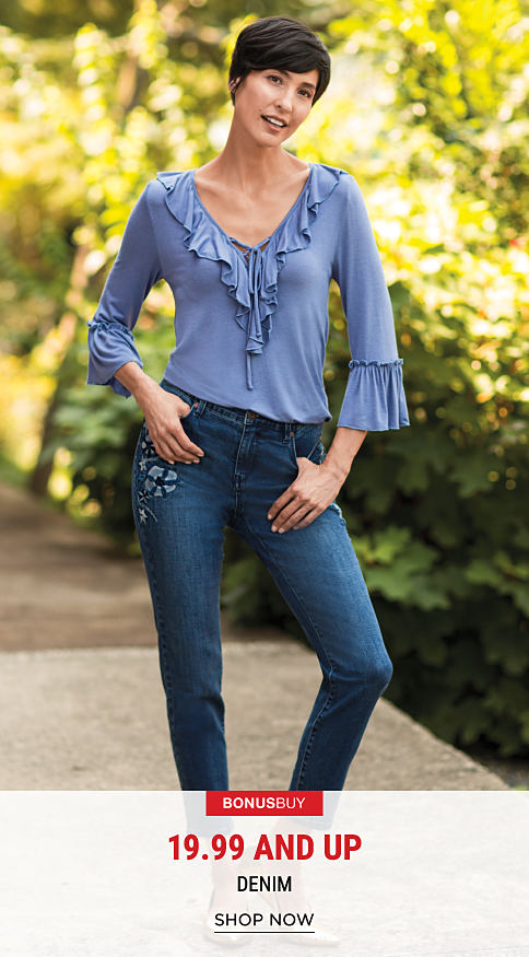 A woman wearing blue jeans & a blue top with ruffle neck detail. Bonus Buy. 19.99 & up denim. Shop now.