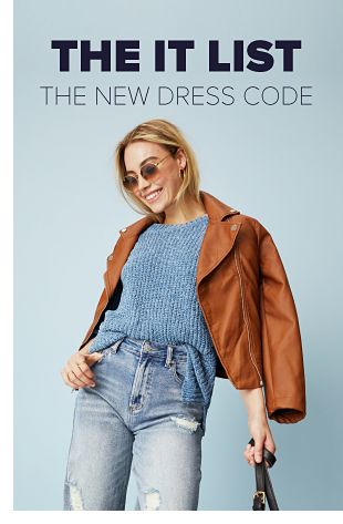 A woman wearing a blue sweater, a light brown faux leather jacket and jeans with distressing. The IT list. The new dress code.