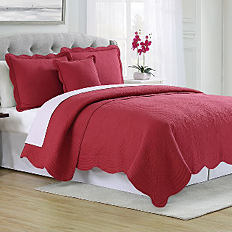 A bed with a red quilt and pillows to match. Shop quilts.
