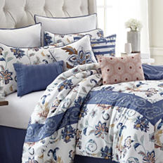 A bed with a printed comforter and pillows to match. Shop bed in a bag.