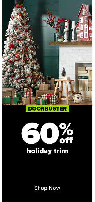 A decorated green snow frosted christmas tree beside a white brick fireplace beside green walls. Presents fill under the christmas tree, and a collection of tiered white candels sit on a wood shelf above the fireplace. Doorbuster 60% off holiday trim. Shop now.
