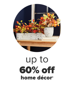 A table with two harvest themed center pieces on top. Up to 60% off home decor.