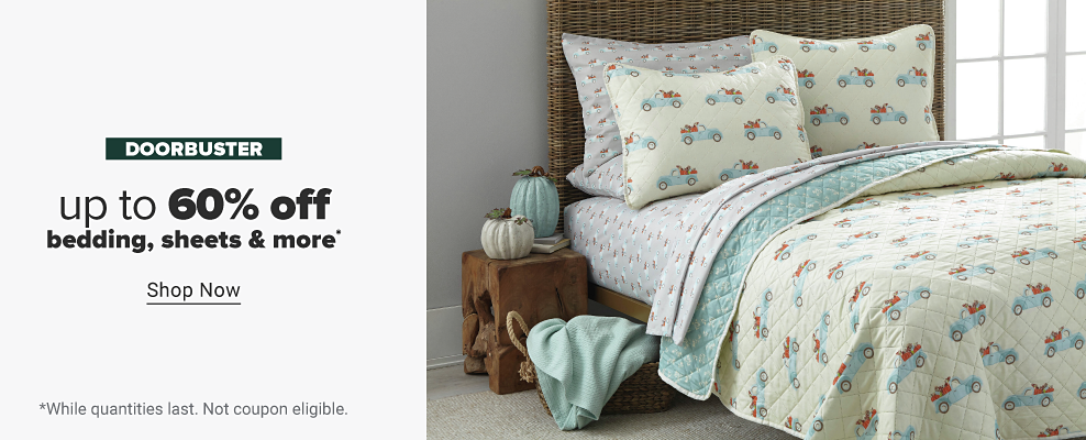 A bedding set featuring a reversible quilt with a fall print featuring a blue truck on one side and a matching blue floral print on the reverse side. Also includes matching pillow shams and coordinating bed sheets. Two decorative pumpkins in blue and white sit atop a nightstand next to the bed. A blue blanket inside a basket. Doorbuster. Up to 60% off bedding, sheets and more. Shop now. While quantities last. Not coupon eligible.