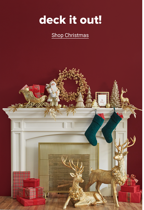 A white fireplace on a red wall is decorated for Christmas featuring a gold wreath, green stockings, golden reindeer and more holiday home decor across the mantle. Deck it out. Shop Christmas.