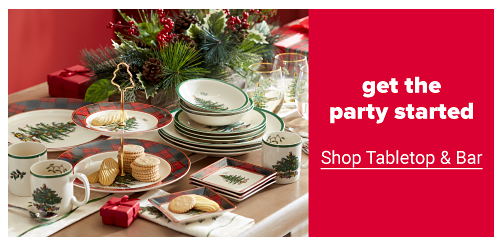 A Christmas-themed tablescape featuring dinner plates, salad plates, bowls and mugs with a Christmas tree design, matching stemless wine glasses, a two-tier holiday serving platter and a centerpiece made of greenery and holly. Get the party started. Shop tabletop and bar.