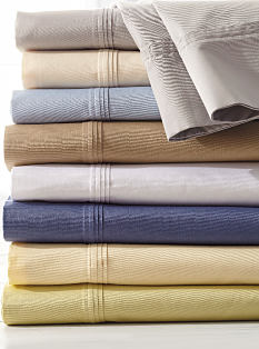 A stack of folded bed sheets in a variety of pastel colors. Shop sheets.
