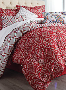 A bed made with a red, gray & white reversible comforter, matching pillows & white sheets. Shop bed in a bag.