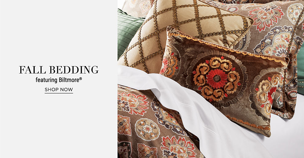 A bed made with a multi-colored comforter, white sheets & an assortment of pillows in a variety of colors & patterns. Fall bedding featuring Biltmore. Shop now.