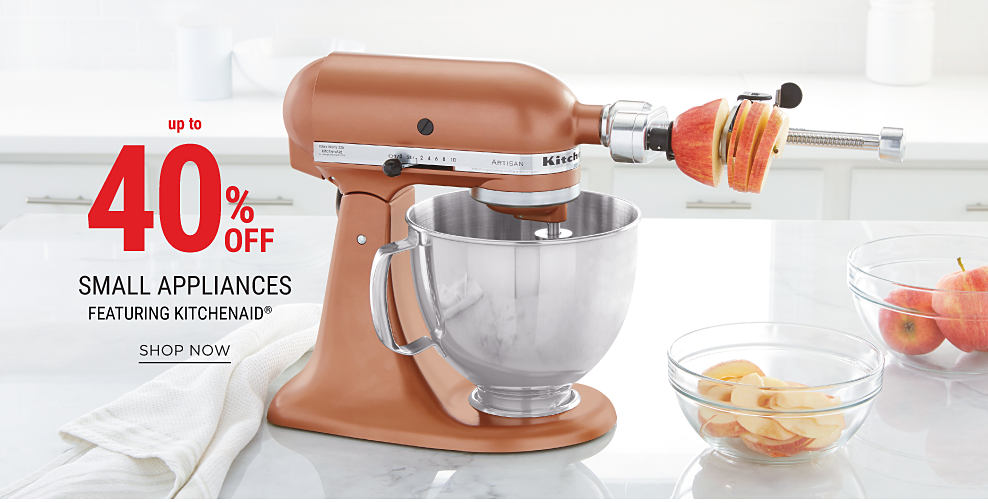 A bronze KitchenAid bowl mixer with spiralizer attachment next to a couple of glass bowls full of sliced apples. Up to 40% off small appliances featuring KitchenAid. Shop now.