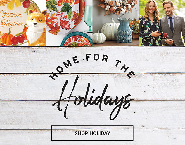A ceramic fox & a fall-themed decorative plat. An assortment of fall-themed dinnerware & drinkware. An assortment of fall-themed home decor. A woman wearing a multi-colored print dress standing next to a man wearing a gray suit, blue dress shirt & navy tie. Home for the Holdays. Shop holiday.