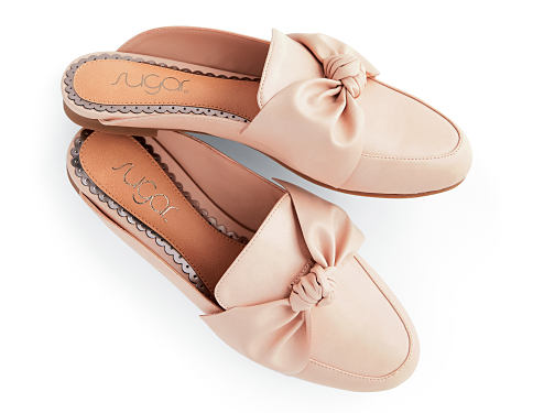 A pair of peach slip-on shoes with bow detail. Boy Meets Girl. Menswear-inspired designs with a feminine twist. Shop now.