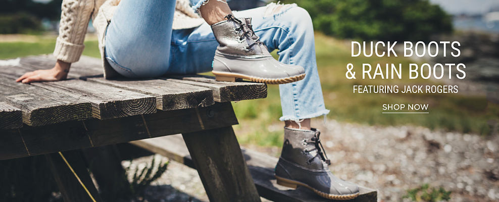 A woman sitting on a picnic table, wearing a white cable-knt sweater, faded blue jeans & duck boots. Duck boots & rain boots featuring Jack Rogers. Shop now.