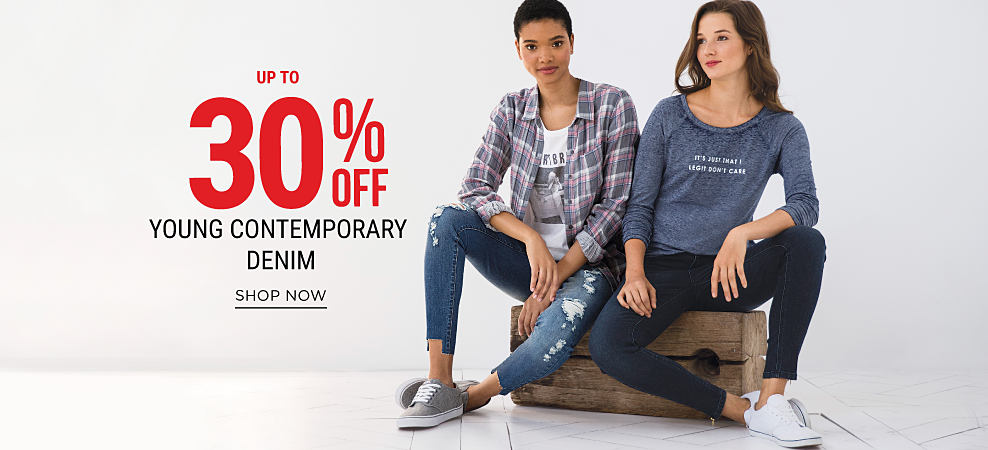 A young woman wearing a multi-colored plaid button-front shirt, a graphic tee, distressed blue jeans & gray sneakers sitting next to a young woman wearing a long-sleeved denim-blue shirt, blue jeans & white sneakers. Up to 30% off young contemporary denim. Shop now.
