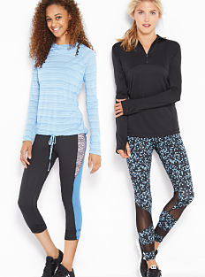 A woman wearing a light blue & white top, navy, light blue & gray yoga pants & black sneakers standing next to a woman wearing a black fleece & a black three-quarter-zip workout jacket, black, blue & white yoga pants & black sneakers. Shop Zelos.
