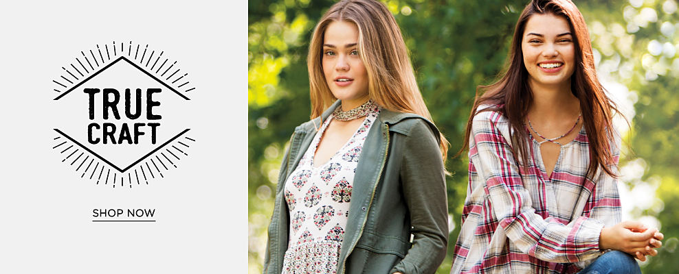 A young woman wearing an olive green military jacket, a multi-colored patterned top & distressed jeans standing next to a young woman wearing a multi-colored plaid top & blue jeans. True Craft. Shop now.