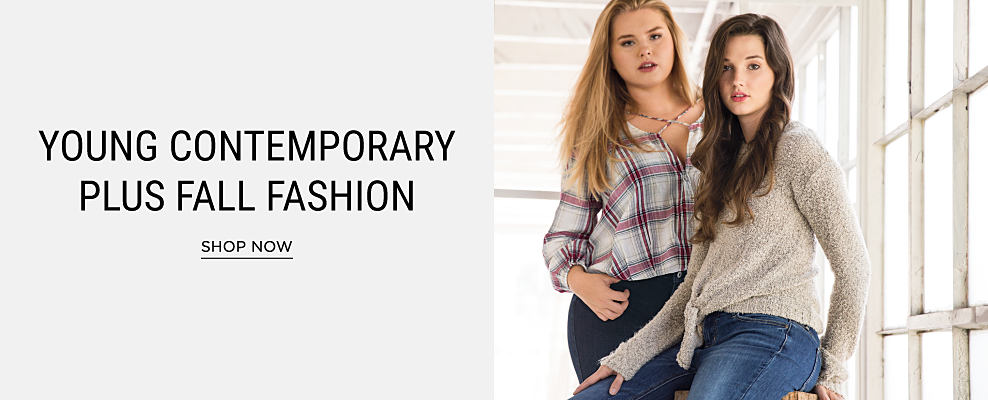 A young woman wearing a multi-colored plaid button-front shirt & black jeans standing next to a young woman wearing a gray sweater & blue jeans. Young contemporary plus fall fashion. Shop now.