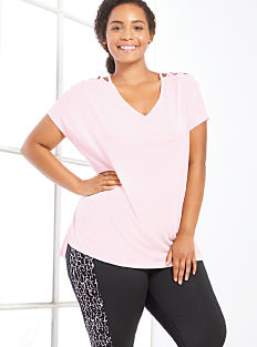 A woman wearing a light pink tee & black workout pants. Shop Zelos.