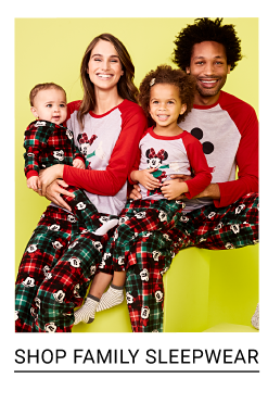 A woman, man & girl wearing matching red, black & white Mickey Mouse pajama tops & multi colored patterned print pajama pants, and a baby wearing a multi colored patterned print onesie. Shop family sleepwear.
