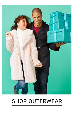 A woman wearing a light pink peacoat over a white top & blue jeans standing next to a man wearing a black coat over a red shirt & black pants holding blue gift wrapped presents. Shop outerwear.
