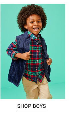 A boy wearing a navy puffer vest over a navy, green & red plaid long sleeved button front shirt & beige pants. Shop boys.