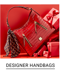 A red croco leather handbag surrounded by red gift wrapped presents. Shop designer handbags.