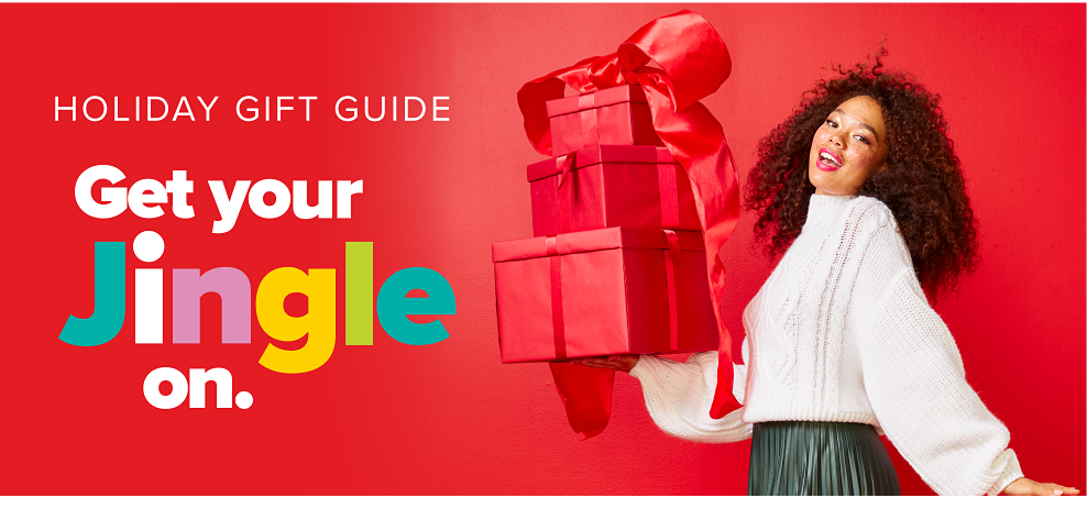 A woman wearing a white blouse, holding presents wrapped in red wrapping paper & bows. Holiday Gift Guide. Get Your Jingle On.
