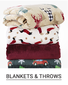 A stack of folded throws in a variety of colors, prints & styles. Shop blankets & throws.