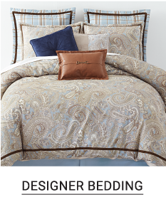 A bed made with a gray comforter & matching pillows. Shop designer bedding.