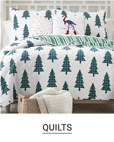 A bed made with a green & white Christmas tree patterned print quilt & matching pillows. Shop quilts