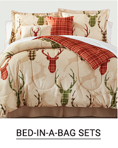 A bed made with a brown & beige deer head patterned print comforter & matching pillows. Shop bed in a bag sets