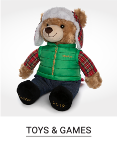 A teddy bear with a winter hat, green puffer vest, green & red plaid shirt, black pants & black shoes. Shop toys & games.