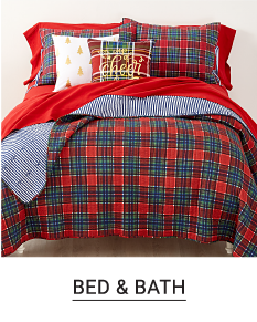 A bed made with a green & red patterned print comforter & matching pillows. Shop bed & bath.