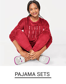 A woman in a red velvet like pajama set and slippers. Shop pajama sets.