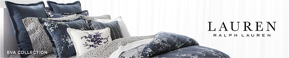 A bed made with a gray & white patterned print comforter & matching pillows. Lauren Ralph Lauren.