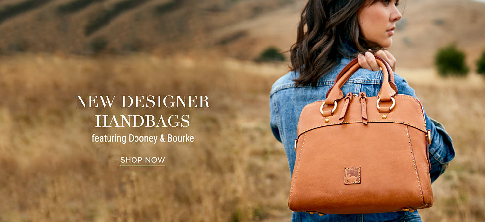 A woman wearing a denim jacket holding a brown leather Dooney & Burke handbag. New designer handbags featuring Dooney & Bourke. Shop now.