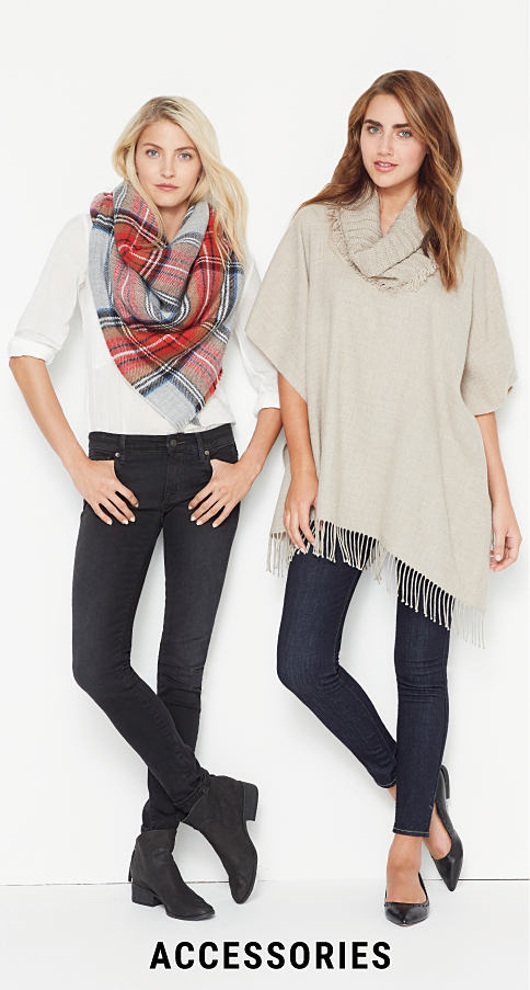 A woman wearing a white blouse, black pants, black boots & a multi-colored plaid scarf wrap standing next to a woman wearing abeige cowl neck poncho, blue jeans & black flats. Accessories. Shop now.