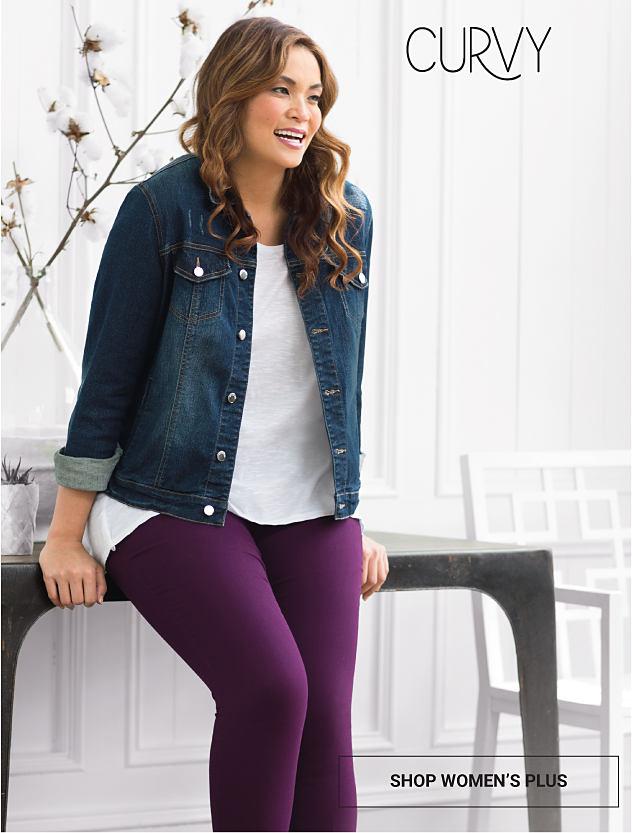 A woman wearing a denim jacket, white top & purple pants. Curvy. Up to 25% off women's fall fashion. Shop women's plus.