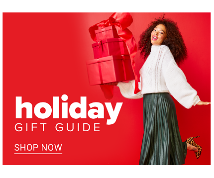 A woman wearing a white blouse & black pants holding presents wrapped in red wrapping paper & bows. Holiday Gift Guide. Get Your Jingle On. Shop now.