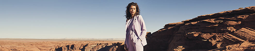 A woman wearing a gray suit. Vince Camuto. Boldly designed stylish shoes, handbags, apparel & accessories that carry you from work to weekend, and office to off duty.