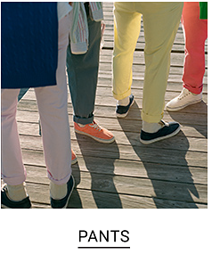 Men standing on a deck wearing polo pants. One is wearing khaki, one is in green, the other is in yellow and the last man has on pink. Shop pants.