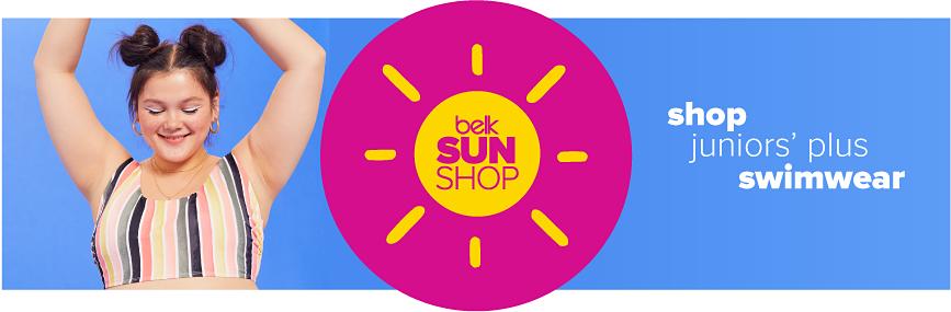A young woman in a navy, light blue, light pink and white swim top. Belk sun shop. Shop juniors' plus swimwear.