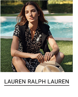 A woman in a black and white dress with a black sweater draped over her shoulders. Lauren Ralph Lauren.