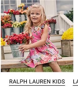 A little girl wearing a pink floral dress. Shop Ralph Lauren Kids.
