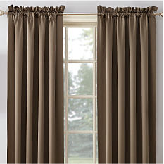 A window with neutral colored curtains. Shop window treatments.