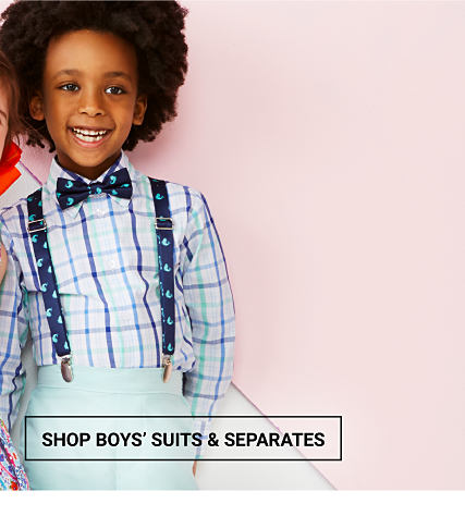 A boy wearing a multi-colored plaid long-sleeved button-front shirt, a black & white bow tie, black & white suspenders & light blue pants. Easter Dresswear for the Family. Up to 50% off. Shop boys suits & separates.