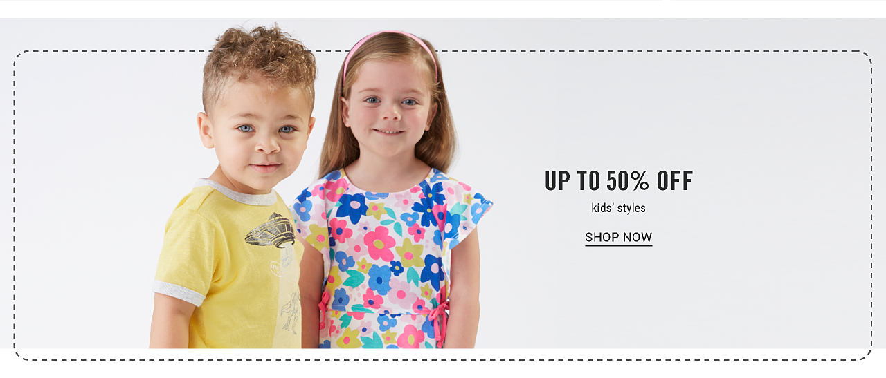 Extra 25% off regular & sale men's & kids fashion with coupon. A boy wearing a yellow T shirt with a white piping & a black & white flying saucer front graphic standing next to a girl wearing a multi colored floral print short sleeved top. Up to 50% off kids styles. Shop now.