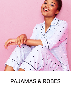 A woman in a white and blue pajama set. Shop pajamas and robes.